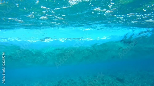 Wall mural Underwater view of the tropical crystal clear breaing wave working like a big lens and refracting the coast view