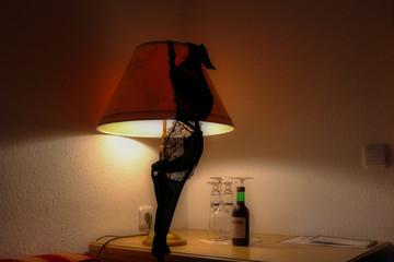Dieses einzigartige Bild zeigt einen schwarzen BH über einer Lampe und davor eine kleine Flasche Rotwein. Dieses Bild wurde in einem Hotel in Bayern Deutschland aufgenommen