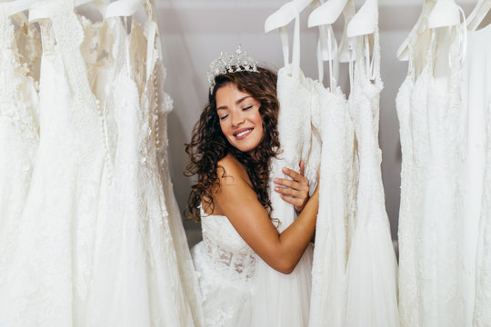 Beautiful young brunette woman choosing wedding dress in a bridal salon.
