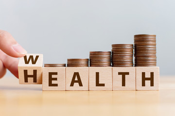Hand flip wooden cube with word wealth to health with coins stack step up growing growth value. Investment in life insurance and healthcare concept Fototapete