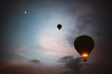 Hot air balloons at sunrise with moon