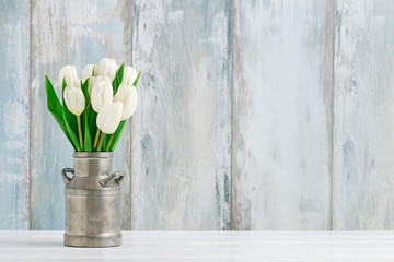 Bouquet of white tulips in vintage silver can.