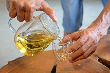 Hand that pours chinese green tea from glass kettle to small cup.