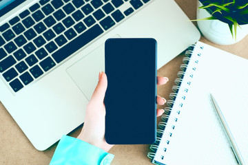 Female hand holding black mobile smart phone with blank screen on laptop computer and notepad background.
