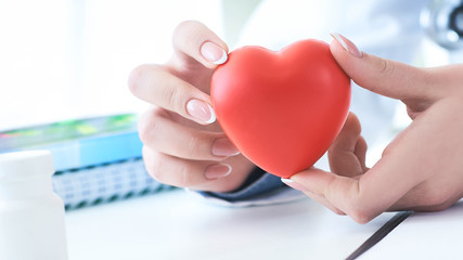 Female medicine doctor hold in hands red toy heart close -up. Cardio therapeutic student education concept