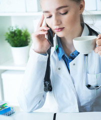 Beautiful young female therapeutic doctor sitting in front of working table with laptop and documents on it calling on the phone and drinking coffee or tea.