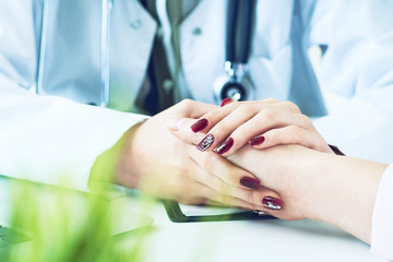 Cropped image of female therapist holding patient's hands during the consultation. Medical ethics and trust concept
