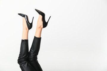 Young woman in high heels on light background