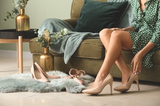 Young woman putting on shoes in room