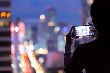 Woman using mobile phone taking cityscape photo at night