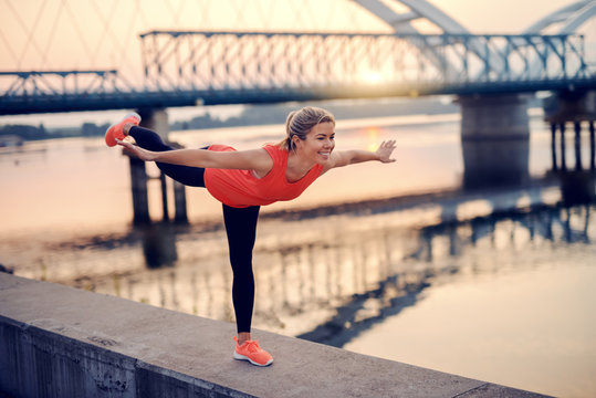Smiling Caucasian blonde woman practicing balance on one leg while standing on the quay. In background bridge. I can and I will.
