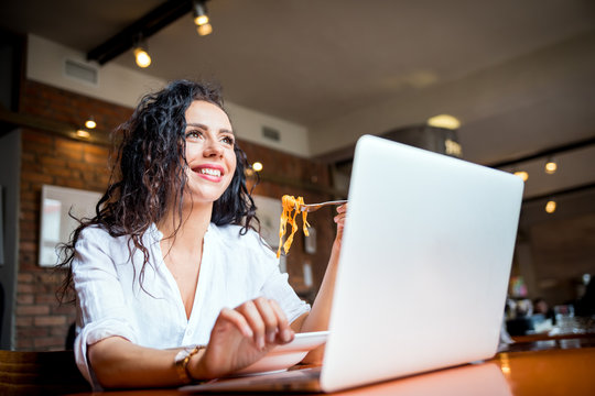 Latin young woman working on laptop computer at restaurant, eating break during work