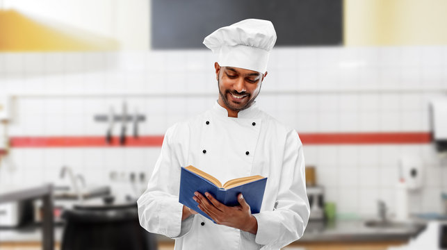 cooking, profession and people concept - happy male indian chef in toque reading cookbook over restaurant kitchen background