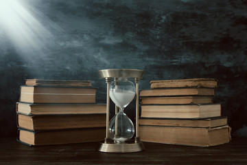 Hourglass as time passing concept and old books in front of black wall background. Conceptual photo on history, fantasy and education