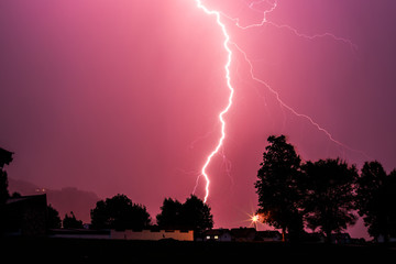 Thunderstorm in the night: Lightning on the colored sky. Global warming.