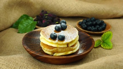 Fototapete - Sprinkle powder sugar on the tower of pancakes in wooden bowl with blueberry and mulberry on sackcloth