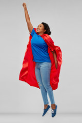 super power and people concept - happy african american young woman in superhero red cape flying up over grey background