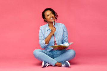 education, high school and inspiration concept - happy african american young student woman with pen and diary or notebook sitting on floor and thinking over pink background