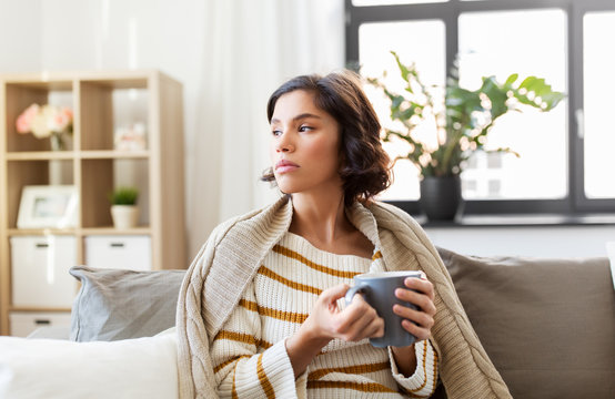 health, cold and people concept - sad sick young woman in blanket sitting on sofa and drinking hot tea at home