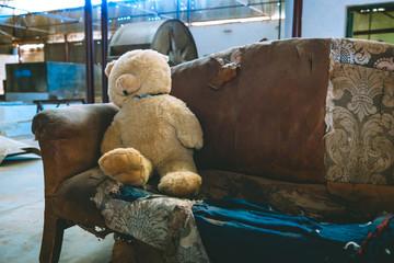 Teddy bear on a vintage sofa in an industrial building