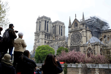 People take pictures of Notre-Dame Cathedral after a massive fire devastated large parts of the gothic gem in Paris