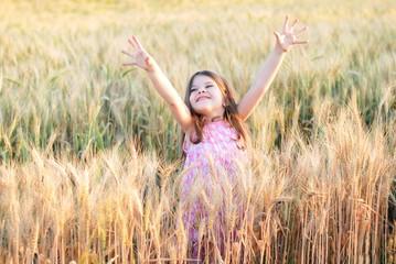 Beautiful little caucasian girl on a wheat field with ripe golden spike and sun backlit. Long haired cute preschooler girl in golden field at sunset. Happy little girl enjoying nature wheat field  Wall mural