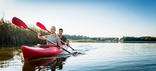 Beautiful couple sailing kayak on lake Wall mural