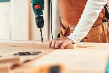 Female carpenter using electric drill Wall mural