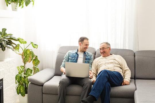 Senior man using laptop PC with his adult son