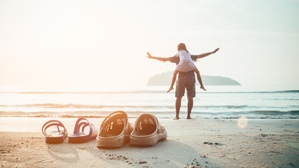 Rubber slippers on the beach with freedom father and daughter standing and watching the sunrise