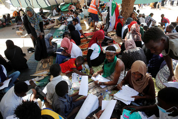 Sudanese demonstrators draw pictures as they rest under a tent in Khartoum