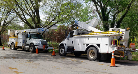 Parked emergency utility vehicles on neighborhood residential street after storm.
