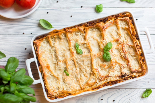 Homemade baked lasagna emiliane made from traditional meat ragù cooked for 4 hours, béchamel sauce, flat pasta. Served in a casserole  and cut into single-serving square portions. Top view.