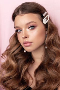 beautiful young woman with dark natural hair and tender makeup with pearl accessories