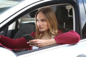 Junge Frau mit Handy am Steuer
