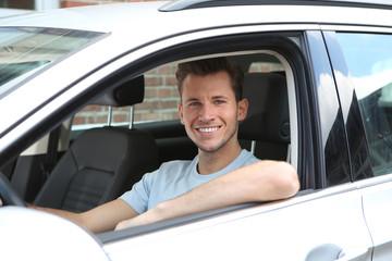 Junger Mann sitzt lachend in einem Auto