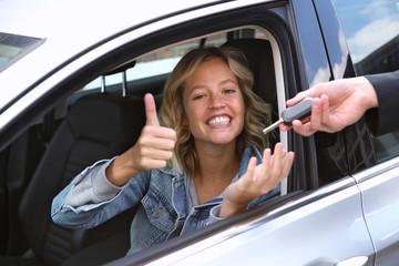 Junge Frau sitzt in einem Auto und bekommt einen Schlüssel überreicht