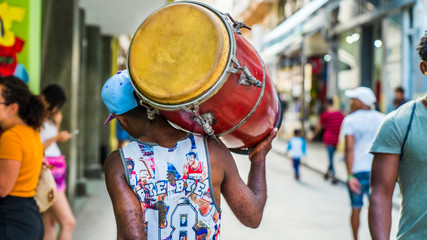 Havana, Cuba. Man walks down the street carrying his drum on his shoulder.
