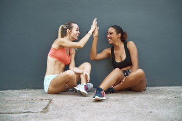 Wall Mural - Laughing friends high fiving during a break from their workout