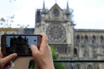 A man takes pictures of Notre-Dame Cathedral after a massive fire devastated large parts of the gothic gem in Paris