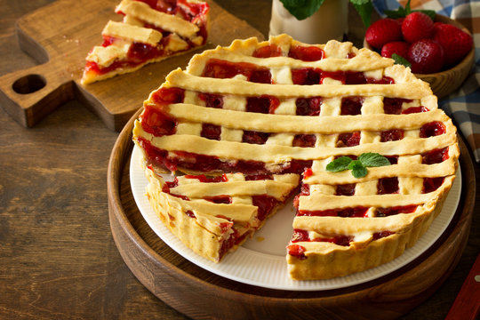 Berry pie summer. Sweet pie, tart with fresh berry strawberries on a rustic kitchen table. Delicious cake with strawberries. Copy space.