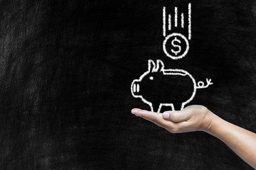 Saving Pig and Falling Coin Drawing on Hand with Old Chalkboard Background, Suitable for Saving and Deposit Concept Presentation.