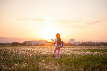 free creative little girl with long hair playing guitar and singing song outdoor sunset summer field on background of beautiful city