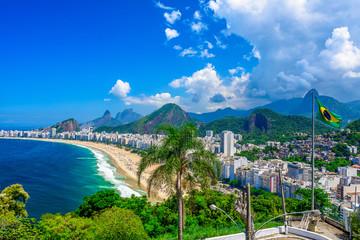 Fotomurales - Copacabana beach in Rio de Janeiro, Brazil. Copacabana beach is the most famous beach of Rio de Janeiro, Brazil. Skyline of Rio de Janeiro with flag of Brazil