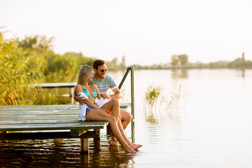 Loving couple sitting on the pier on lake