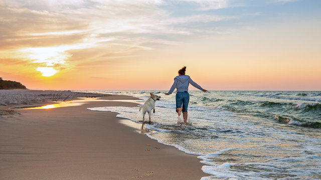 Happy woman on the beach with a dog