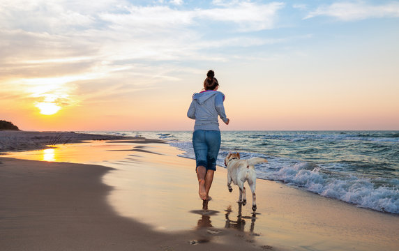 A woman running on the beach with a dog