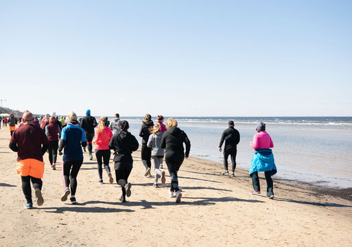 A group of back lit people in colorful outfits are running during a marathon that goes partly over a beach in Jurmala, Latvia 14 April 2019