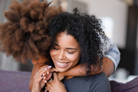 Close up smiling African American mother embracing with daughter