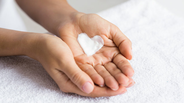 Love your body. Female hands with cream in heart shape